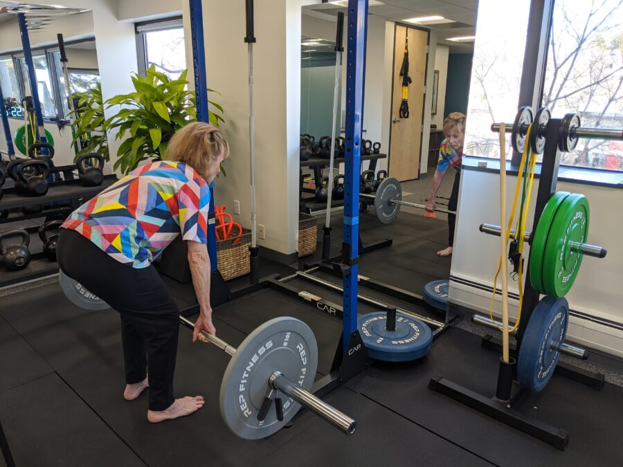 Older woman in physical therapy lifting weight